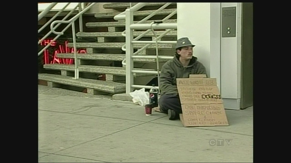A Windsor panhandler sits on the sidewalk on Ouellette Avenue on Sunday, May 26, 2013.