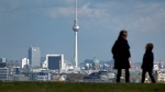 A woman and a young boy walk in front of Berlin's skyline on top of the Drachenberg in Berlin, Germany, Tuesday, Oct. 29, 2013. (AP / Michael Sohn)