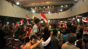 Supporters of Shiite cleric Muqtada al-Sadr storm parliament in Baghdad's Green Zone, Saturday, April 30, 2016. Dozens of protesters climbed over the blast walls and could be seen storming the Parliament building, carrying Iraqi flags and chanting against the government. (AP Photo/Khalid Mohammed)