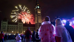People watch fireworks as they explode behind the Peace Tower during Canada Day celebrations on Parliament Hill on Friday, July 1, 2016 in Ottawa. (Justin Tang / THE CANADIAN PRESS)