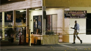 An investigator walks near the scene of a fatal shooting at Club Blu nightclub in Fort Myers, Fla., on July 25, 2016. (Kinfay Moroti / The News-Press via AP)