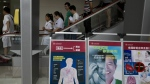 Hospital staff and visitors past by boards warning of the damage to human organs from smoking at the Beijing Chaoyang Hospital, one of the hospitals approved for organ transplants, in Beijing, China on Wednesday, Aug. 24, 2016. (AP / Ng Han Guan)